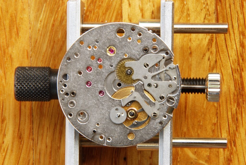 UK watchmaker showing service of Omega Speedmaster - hour recorder runner and hammer mounted