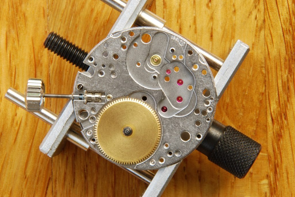 UK watchmaker showing service of Omega Speedmaster - barrel fitted to plate
