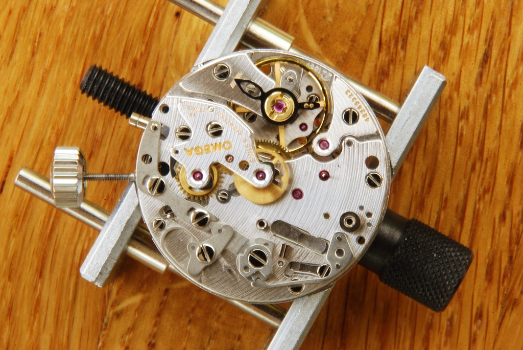 UK watchmaker showing service of Omega Speedmaster - chronograph bridge fitted