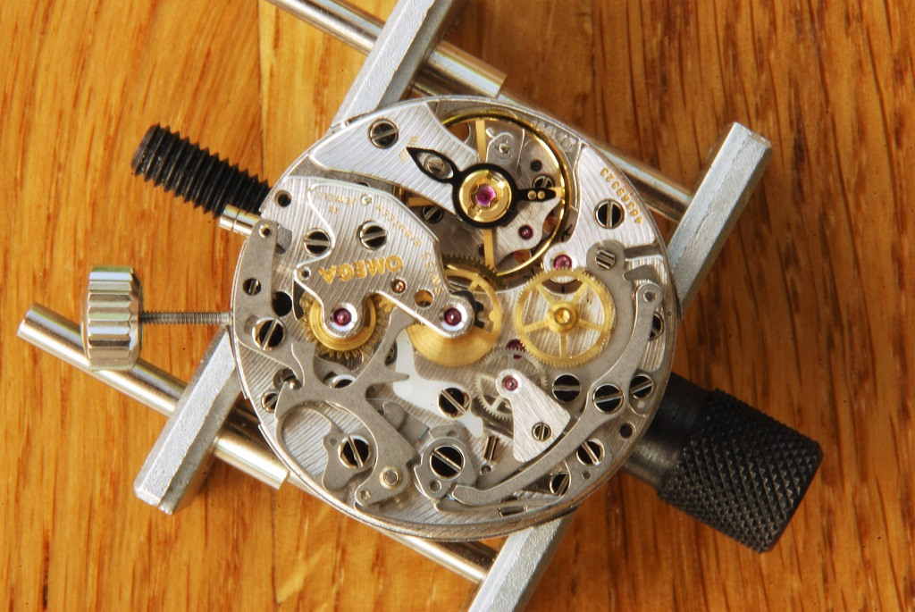 UK watchmaker showing service of Omega Speedmaster - hour recorder yoke fitted