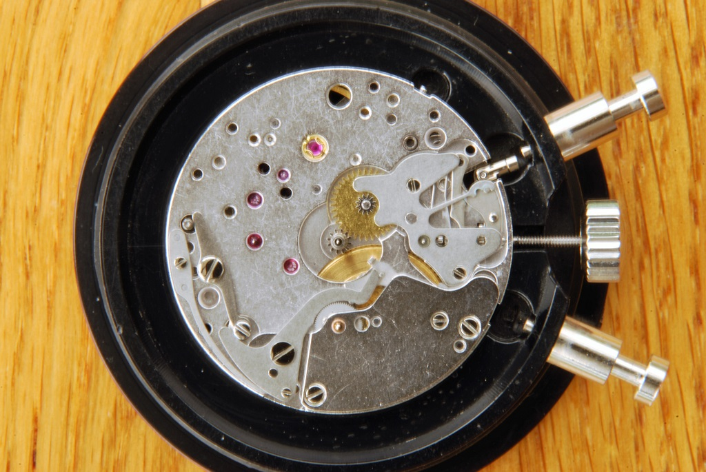 UK watchmaker showing service of Omega Speedmaster - dial side showing hour recorder switch fitted