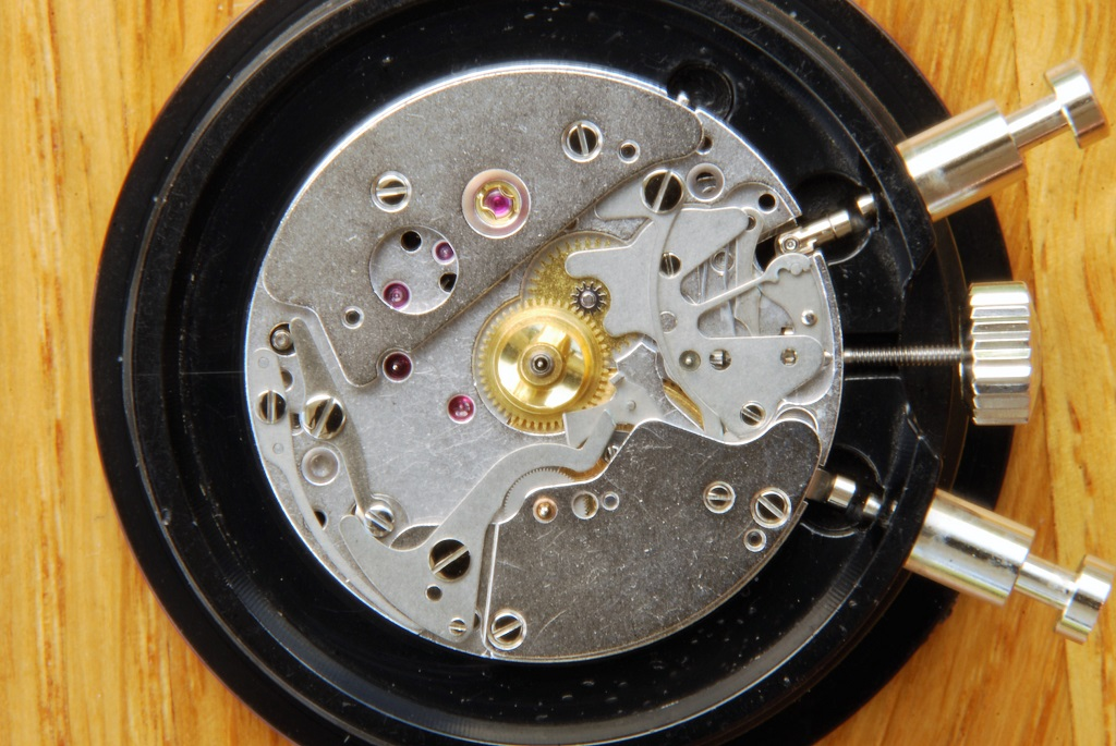 UK watchmaker showing service of Omega Speedmaster - dial side showing hour wheel fitted
